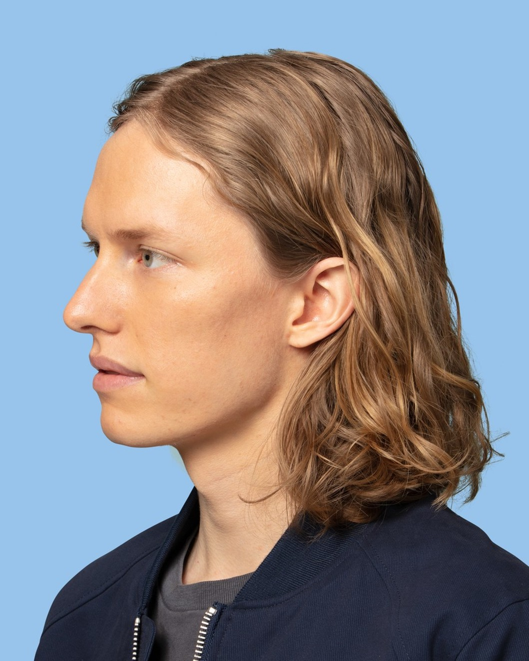 Guy with mid-length wavy hair using the product