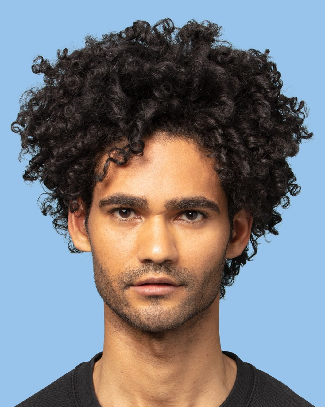Guy with curly hair using the product